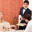 Waiter serving young couple — Stockfoto #7794826