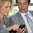 Stock Photo: Pair of executives looking at something on cellphone