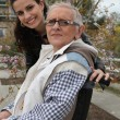 Stockfoto: Young wompushing elderly lady in wheelchair