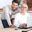 Young man helping senior woman with a laptop compute — Foto de Stock