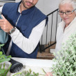 Young man and older woman watering plants — Stock Photo #7796838