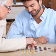 Young man paying game with old lady — Stock Photo