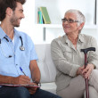 Senior woman talking to a young medic — Stock Photo #7796855