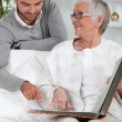 Elderly person looking at photos with son — Stock Photo #7796910