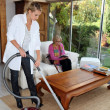 Girl vacuuming for an elderly woman — Stock Photo