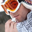 Young skier putting cold cream lip stick on his lips - Stockfoto