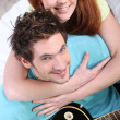 图库照片: Young couple at home with guitar