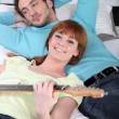 Young couple relaxing with a guitar at home — Stock Photo #7797568
