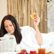 Woman having breakfast and reading newspaper — Stock Photo