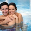Happy couple hugging in a swimming-pool — Stok fotoğraf