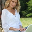 Woman on laptop under tree — Stock Photo #7797915