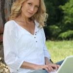 Woman on laptop under tree — Stock Photo