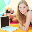 Portrait of a woman on the beach with laptop — Stock Photo