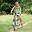 Blond teenage girl on bike ride — Stock Photo
