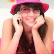 Girl in a shocking pink hat making a call on the beach - Stock Photo