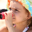 Little girl on the beach with binoculars - Стоковая фотография