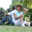 Couple with bikes sitting on the grass — Stock Photo