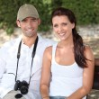 Couple sitting on a bench with a camera — Stock Photo #7798872