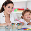 Foto Stock: Female adult and child girl drawing