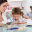 Woman and child colouring at a desk - Stock Photo