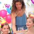 Mother bringing a cake at a birthday party — Stock Photo