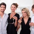 Stock Photo: Four toasting in front of a Christmas tree