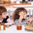 Two children at kitchen table having breakfast — Stock Photo