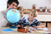 Brother and sister doing geography homework — Stock Photo