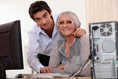 Young man helping an elderly lady use a computer — Stock Photo
