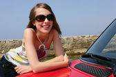 Young woman leaning against a car — Stock Photo