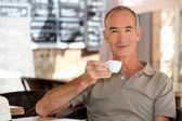 Elderly man having an espresso on a terrace — Stock Photo