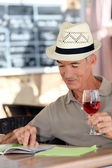 Elderly man drinking a glass of rose in a cafe — Stock Photo