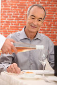 Man being served a glass of rose wine — Stock Photo