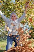Grandmother playing with a heap of dead leaves — Stock Photo