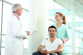Invalid person in wheelchair with staff members of hospital — Stock Photo