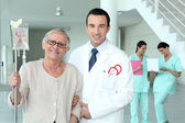 Doctor helping his patient walk — Stock Photo