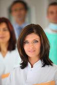 Genç kadın arka planda tıbbi ekiple portresi — Stok fotoğraf