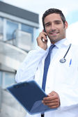 Doctor using his mobile phone outside a hospital building — Stock Photo