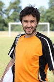 Male footballer stood in front of pitch — Stok fotoğraf