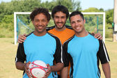 Three young footballers in front of goal — Stok fotoğraf