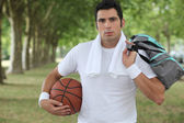 30 years old sportyman holding a basket ball and a sports bag — Stock Photo
