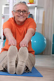 Senior woman doing floor exercises — Stock Photo