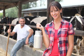 Kobieta z rezygnacji z mleka przed stado krów — Zdjęcie stockowe