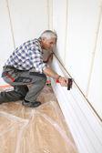Man putting up interior wood cladding — Stock Photo