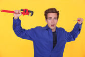 Shocked man stood with wrench and screwdriver — Stock Photo