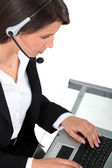 Young woman wearing a headset typing at a keyboard — Stock Photo