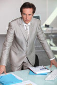 Businessman leaning on table — Stock Photo