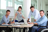 Man in wheelchair sat at desk with colleagues — Stock Photo