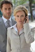 商人和使用电话的女人. — 图库照片
