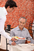 Waitor serving food — Foto Stock
